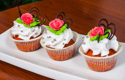 Cupcakes decorated with pink rose on wooden background Stock Photos