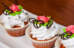 Cupcakes decorated with pink rose on wooden background Royalty Free Stock Photos