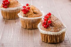 Cupcakes decorated with red currant on a wooden background/Cupcakes decorated with red currant on a wooden background. selective. Cupcakes decorated with red royalty free stock image