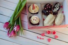 Cupcakes en eclair in vakje leggen op lijst dichtbij tulpen Stock Fotografie