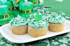 Cupcakes in a Festive St. Patrick's Day Setting. Four decorated cupcakes in a festive St. Patrick's day setting with shamrocks and fedoras Stock Image