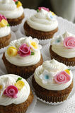 Cupcakes with fondant flowers. Carrot cupcakes decorated with colorful fondant flowers stock photography