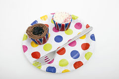 Cupcakes and fork in multicolored plate against white background Stock Photos