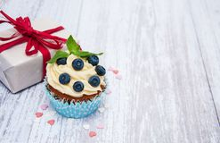 Cupcakes with fresh berries and gift box. On a old wooden table Stock Photography