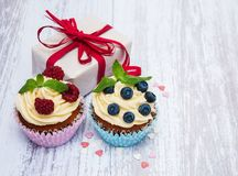 Cupcakes with fresh berries and gift box. On a old wooden table Stock Image