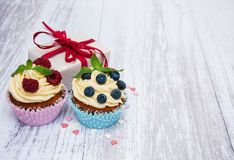 Cupcakes with fresh berries and gift box. On a old wooden table Royalty Free Stock Photos