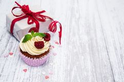 Cupcakes with fresh berries and gift box. On a old wooden table Royalty Free Stock Images