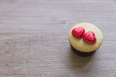 A cupcakes with heart shape chocolate on wooden table Royalty Free Stock Photos