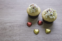 A cupcakes with heart shape chocolate on wooden table Royalty Free Stock Photo
