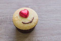 A cupcakes with heart shape chocolate on wooden table Stock Photo