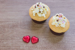 A cupcakes with heart shape chocolate on wooden table Stock Images