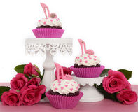 Cupcakes with high heel stiletto fondant shoes. International Womens Day, March 8, cupcakes with high heel stiletto fondant shoes on cake stands on vintage pink stock photos