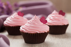 Cupcakes homemade sweet pastry with pink buttercream and red hearts in row on vintage cloth background. Royalty Free Stock Photo