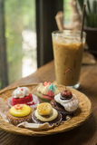 Cupcakes with iced latte. On old wooden table Stock Image