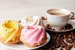 Cupcakes with icing and cup of coffee with milk. Royalty Free Stock Photography