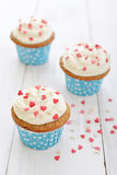 Cupcakes. With icing in shape of hearts on wooden background Stock Photos