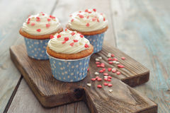 Cupcakes. With icing in shape of hearts on wooden background Royalty Free Stock Photos