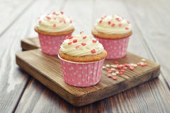 Cupcakes with icing. In shape of hearts on wooden background Stock Photography