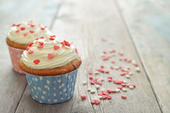 Cupcakes. With icing in shape of hearts on wooden background Stock Photography