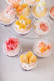 Cupcakes with individual wedding decoration. At white table Stock Photo
