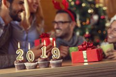 Welcome New 2019 Year. Cupcakes with lit candles shaped as numbers 2019 placed on a coffee table with group of friends celebrating and exchanging gifts in the royalty free stock photography