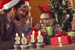Welcome New 2019 Year. Cupcakes with lit candles shaped as numbers 2019 placed on a coffee table with group of friends celebrating and exchanging gifts in the stock photography