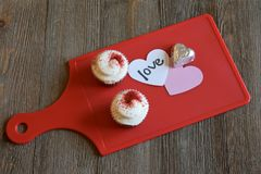 Cupcakes and loving sentiment on a wood background. Sweet treats on a red board and checkered towel Stock Photos