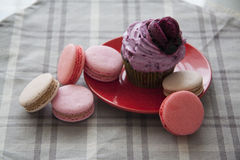 Cupcakes and macarons on grey tablecloth Stock Image