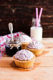 Cupcakes with mascarpone cream cheese, black currant jelly jam and freshly shredded coconut on a wooden table with a bottle of mil stock images