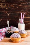 Cupcakes with mascarpone cream cheese, black currant jelly jam and freshly shredded coconut on a wooden table with a bottle of mil stock photos