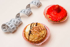 Cupcakes with measuring tape on table Royalty Free Stock Photos