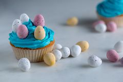 Cupcakes met blauw suikerglazuur met suikergoedpaaseieren op een wit marmer worktop royalty-vrije stock foto's