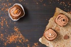 Cupcakes met chocoladeroom is verfraaid op een donkere rustieke achtergrond Hoogste mening, exemplaarruimte royalty-vrije stock afbeelding