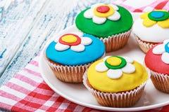 Cupcakes met kleurrijke mastiek wordt verfraaid die Stock Afbeelding
