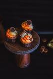 Cupcakes met room in een donker die glas, met chocolade wordt verfraaid, de koekjes bevinden zich op een tribune van donker hout  Stock Fotografie