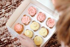 Cupcakes met roze en gele room in document vakje op bruine backgr Stock Afbeeldingen