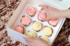 Cupcakes met roze en gele room in document vakje op bruine backgr Royalty-vrije Stock Foto