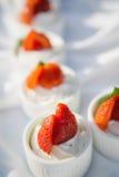 Cupcakes met slagroom met aardbei wordt verfraaid die Stock Foto