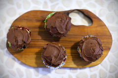 Cupcakes or muffins covered with chocolate cream Stock Photos
