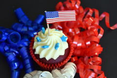 Cupcakes or muffins decorated with american flag. Happy Independence Day, celebration, patriotism and holidays concept - close up of glazed cupcakes or muffins Stock Photography