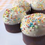 Cupcakes. On a orange tartan tablecloth Stock Photos
