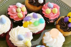 Cupcakes with oval eggs. On buttercream icing Stock Images