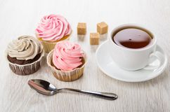 Cupcakes with pink and brown cream, cup of tea, sugar. Cupcakes with pink and brown cream, cup of tea, lumpy sugar and teaspoon on wooden table Stock Photo