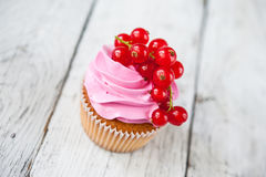 Cupcakes with pink cream and red currant Royalty Free Stock Images