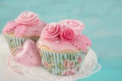 Cupcakes with pink flowers. On a blue wooden background stock photos