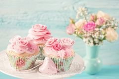 Cupcakes with pink flowers. On a blue wooden background royalty free stock images