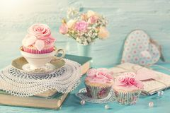 Cupcakes with pink flowers. Retro vintage still life royalty free stock photo