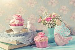 Retro vintage still life. Cupcakes with pink flowers. Retro vintage still life stock photos
