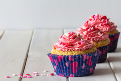 Cupcakes and Pink Frosting on Table with Copy Space Stock Image