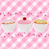 Cupcakes on pink gingham. Cupcakes decorated with icing and a cherry on a pink gingham background Stock Photography